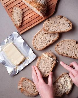 Flache hände, die butter auf brotscheiben verteilen