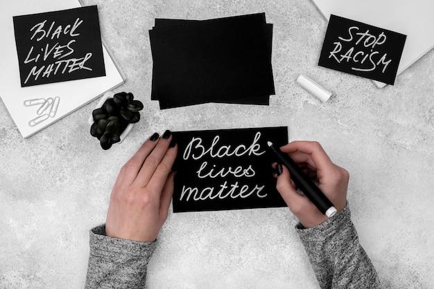 Flache hände, die schwarze lebensmaterie auf karte schreiben
