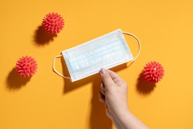 Flache handlage, die medizinische maske mit viren hält