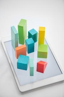 Flache hölzerne, orange und grüne flache hölzerne steine und würfel, die diagramm auf touchpad-bildschirm über weißem hintergrund symbolisieren