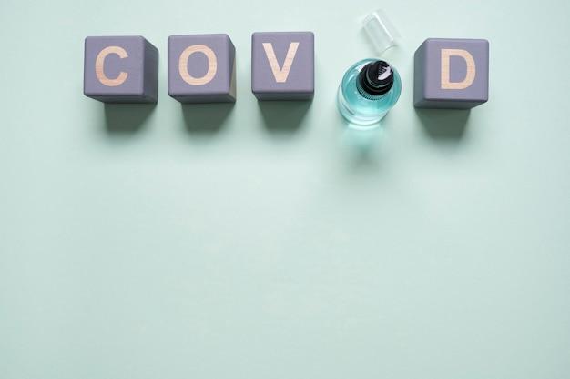 Flache holzwürfel mit covid und händedesinfektionsmittel