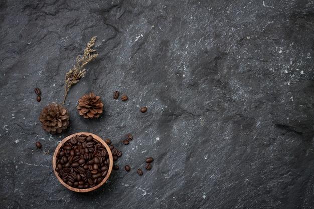 Flache kaffeebohnen in holztasse legen, kiefer und blume trocken auf schwarzem stein