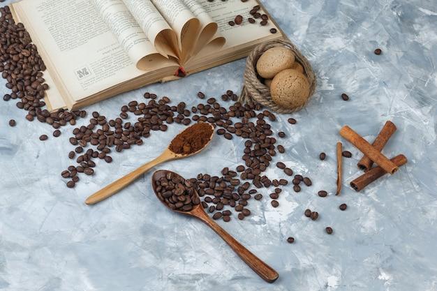 Flache kaffeebohnen, instantkaffee in holzlöffeln mit buch, zimt, keksen, seilen auf dunklem und hellblauem marmorhintergrund. horizontal