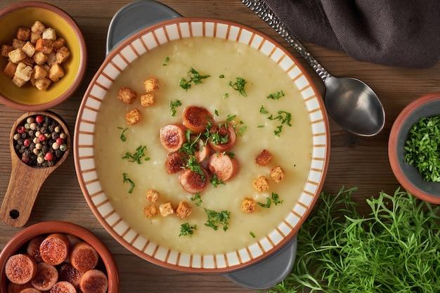 Flache kartoffelcremesuppe mit croutons, gebratenen wiener würstchen und grünem koriander im dunkeln