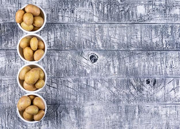 Flache kartoffeln in schalen auf grauem holztisch legen