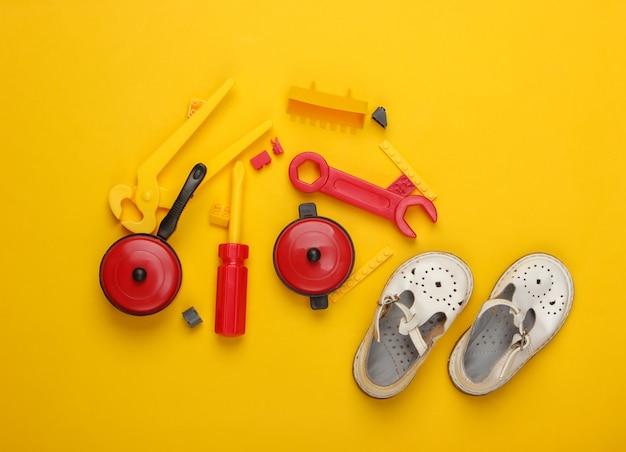 Flache komposition aus kindersandalen und spielzeug auf gelb.