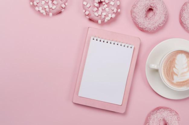Flache komposition mit donuts, notizblock und tasse kaffee auf pink
