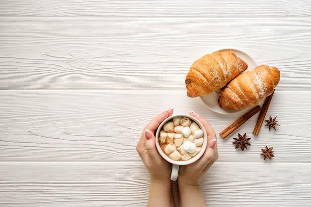 Flache komposition mit einem becher kakao in weiblichen händen und croissants auf einer platte.