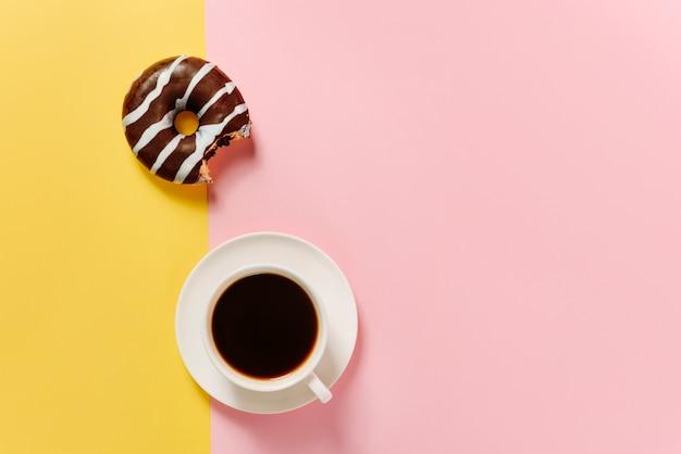 Flache komposition mit einem gebissenen schokoladendonut und einer tasse kaffee