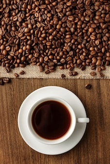 Flache komposition mit einer tasse heißem kaffee und kaffeebohnen