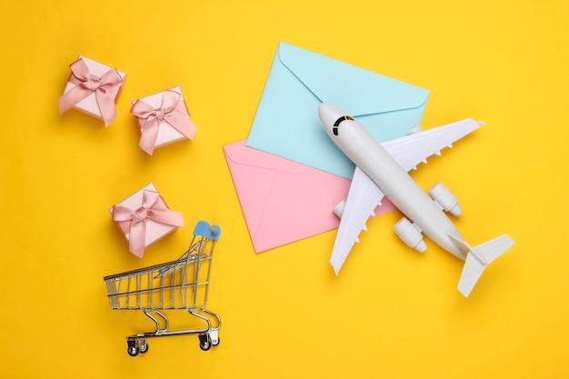 Flache komposition mit flugzeugfigur, geschenkboxen, einkaufswagen und briefumschlägen auf gelb.