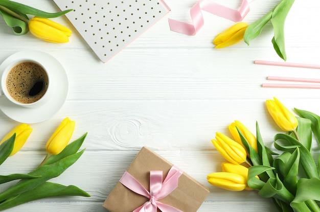 Flache komposition mit gelben tulpenblüten und geschenkbox auf holz. platz für text