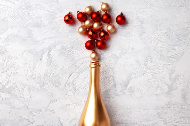 Flache komposition mit goldener champagnerflasche und weihnachtskugeln