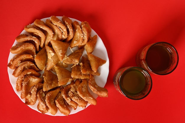 Flache komposition mit orientalischem marokkanischen dessert auf teller neben zwei gläsern im arabischen stil auf rotem hintergrund mit kopierraum. arabische traditionelle orientalische süßigkeiten auf dem festlichen tisch