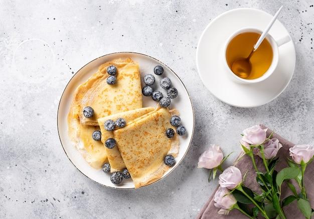 Flache komposition mit schönem frühstück. leckere dünne pfannkuchen