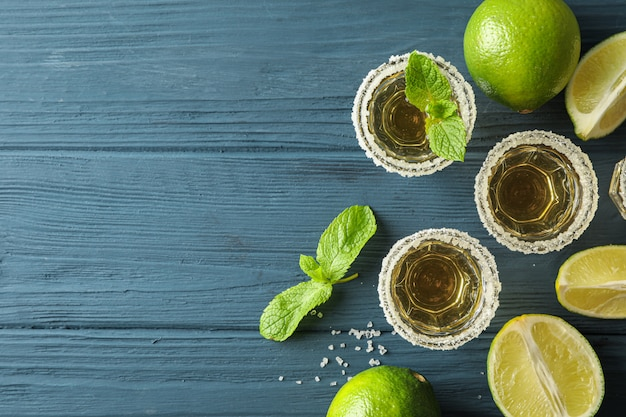 Flache komposition mit tequila, salz, limettenscheiben und minze auf holztisch
