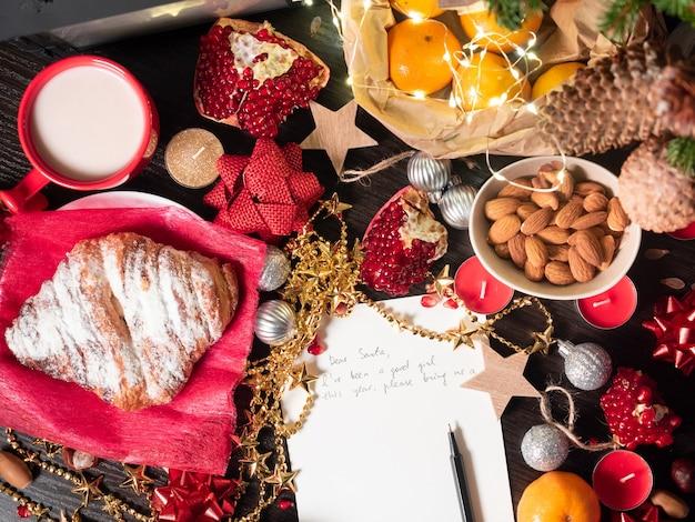 Flache komposition mit weihnachtsdekoration und brief an den weihnachtsmann auf dem tisch