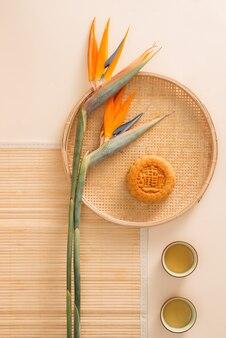 Flache konzeptionelle mitte herbstfest mooncake tea party tischplatte geschossen auf stimmungsvollem rustikalem hintergrund. übersetzung auf runder mondkuchen