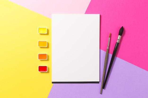 Flache kunstkomposition mit skizzenbuch, pinseln und aquarellfarbe.