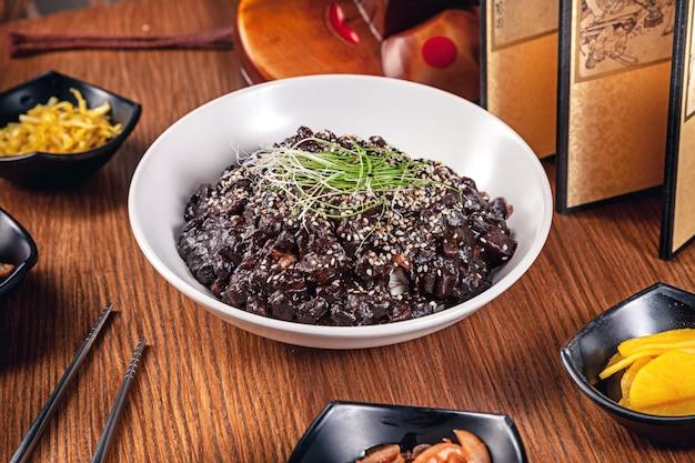 Flache lag koreanisches traditionelles essen mit kimchi auf hölzernem hintergrund. koreanische nudeln mit schwarzer sauce, zwiebeln, roter sauce und sesam, hühnerfleisch. traditionelle asiatische küche. mittagessen. gesundes essen