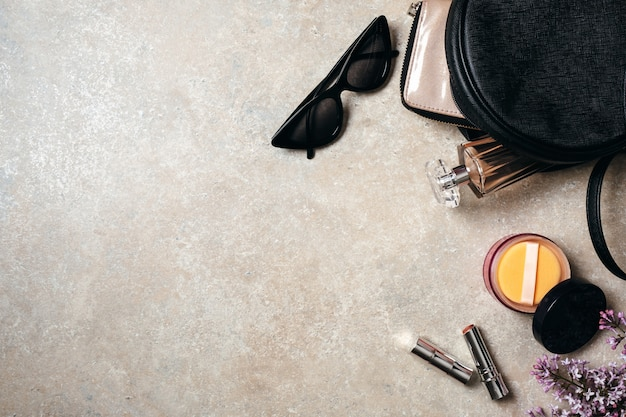 Flache lag moderne minimale arbeitsbereich schreibtisch mit sonnenbrille, ledertasche, brieftasche, frau kosmetik, frühling lila blumen auf beton stein hintergrund.