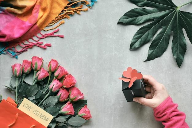 Flache lage, anordnung mit rosenstrauß und exotischem pflanzenblatt.