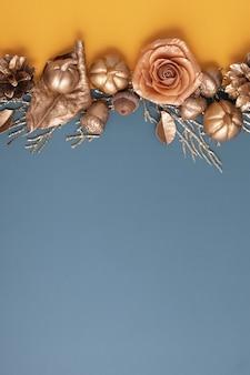 Flache lage aus goldenen eicheln, zapfen, blättern und kürbissen auf buntem hintergrund. minimalistisches herbstkonzept mit kopienraum. hochformat