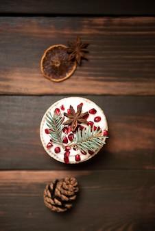 Flache lage cupcake mit tannenzapfen und getrockneten zitrusfrüchten