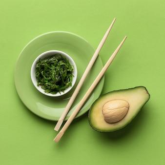 Flache lage der avocado mit schüssel des grüns