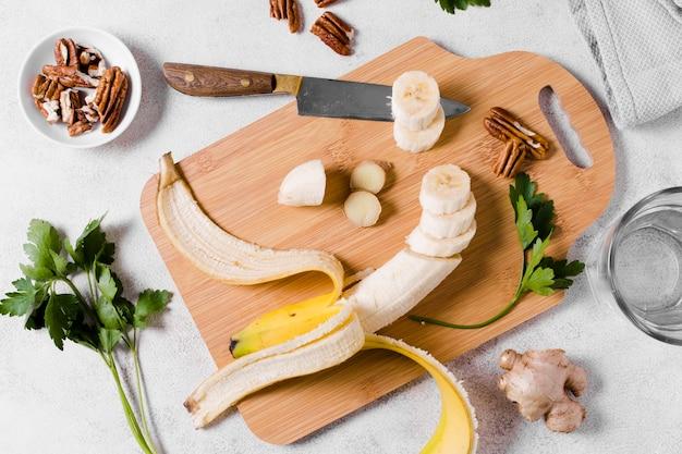 Flache lage der banane auf schneidebrett mit ingwer