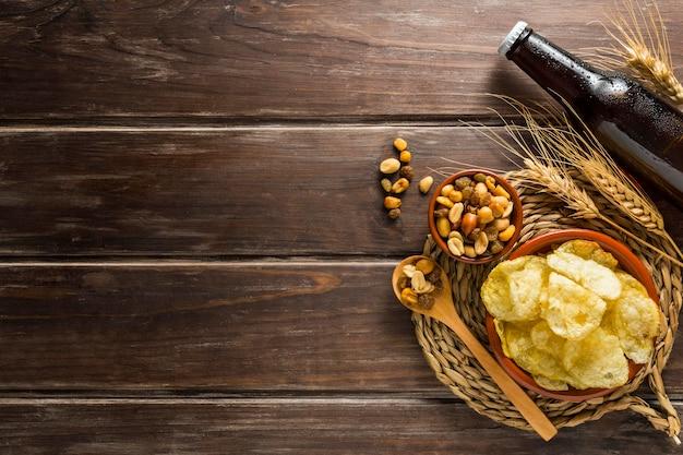 Flache lage der bierflasche mit pommes und nüssen