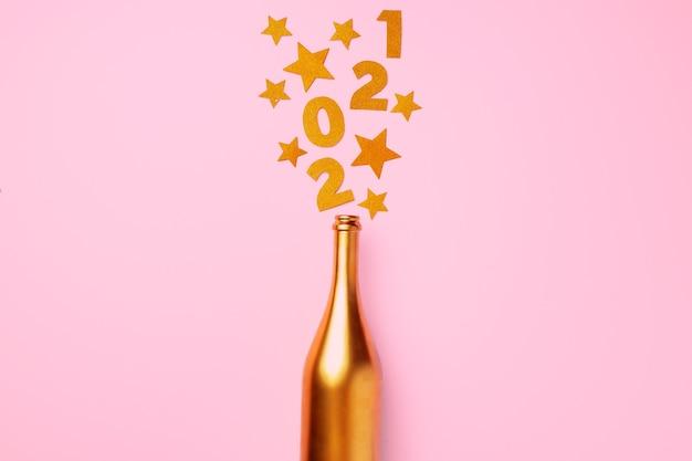 Flache lage der champagnerflasche mit konfetti-schrift 2021