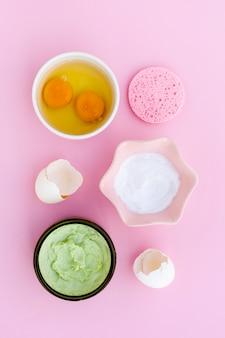 Flache lage der creme und der eier auf rosa hintergrund