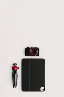 Flache lage der digitalen ausrüstung von kamera-tablet und stativ