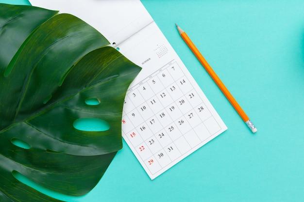 Flache lage der draufsicht des arbeitsplatzschreibtischs redete büroartikel mit kalender an