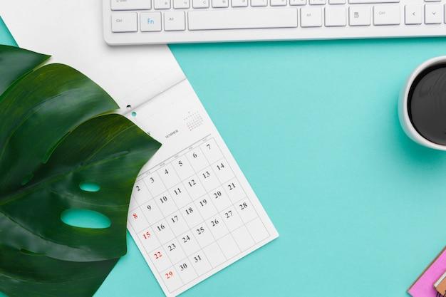 Flache lage der draufsicht des arbeitsplatzschreibtischs redete designbüroartikel mit kalender an