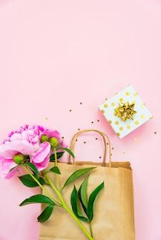 Flache lage der einkaufstasche, der geschenkbox und der pfingstrosenblume über rosafarbenem hintergrund. platz kopieren.