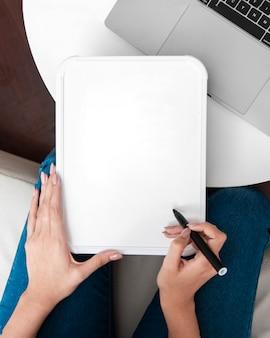 Flache lage der frau, die whiteboard mit stift hält