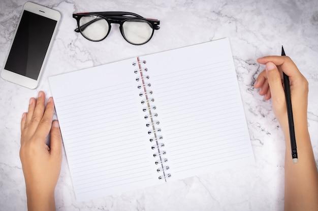 Flache lage der frauenhandschrift in einem notizbuch der leeren weißen seite auf weißem marmorschreibtisch