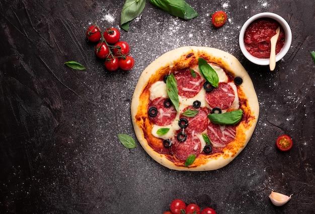 Flache lage der frisch gebackenen pizza mit oliven und basilikum und zutaten auf einem schwarzen hintergrund