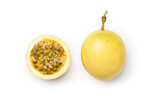 Flache lage der gelben passionsfrucht mit halbiertem schnitt lokalisiert auf weißem hintergrund. beschneidungspfad.