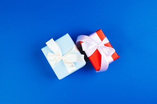 Flache lage der geschenkbox verziert mit bogen auf blauem hintergrund