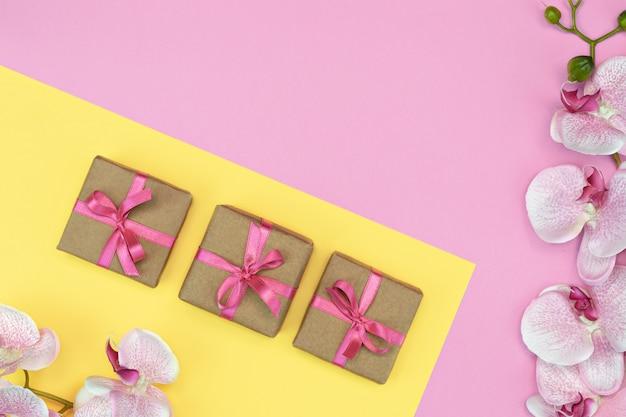 Flache lage der geschenkboxen mit rosa band und orchideenblüten