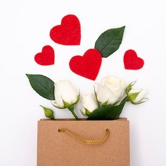 Flache lage der geschenktüte mit rosen und herzen