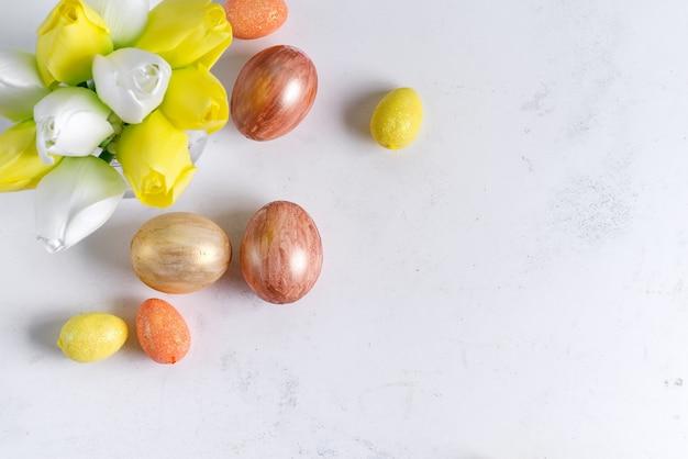 Flache lage der goldenen ostereier mit tulpen auf steinmarmorhintergrund. osterhintergrund oder osterkonzept.
