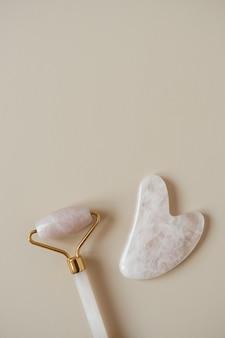 Flache lage der gua-sha-massagerolle und des steinschaberwerkzeugs auf neutralem beige