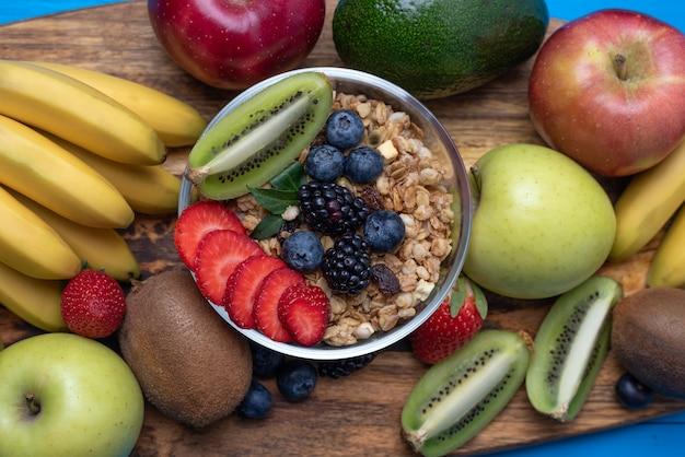 Flache lage der hellen sortierten früchte, der bananen, der äpfel, der mangofrüchte, der kiwi, der erdbeeren, der blaubeeren, mit getreide zum ein gesundes frühstück