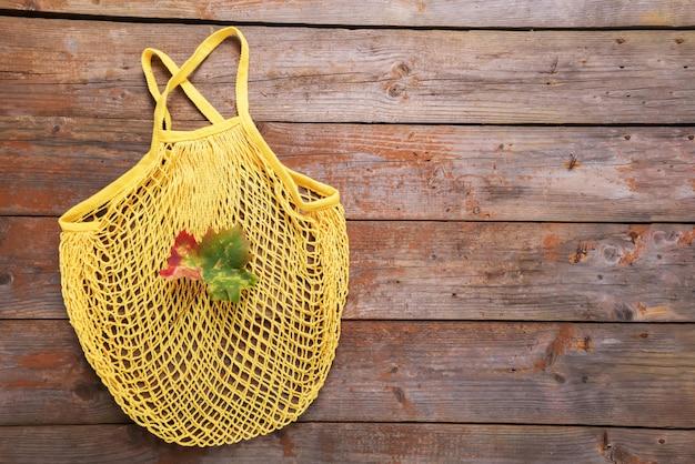 Flache lage der herbstökologie: gelbe schnurtasche aus baumwolle mit einem fallblatt auf alten rustikalen holzbrettern. draufsicht mit kopienraum