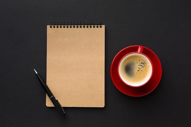 Flache lage der kaffeetasse und des notizbuches auf arbeitsschreibtisch