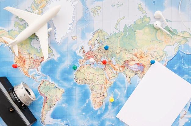 Flache lage der karte mit kamera und spielzeugflugzeug